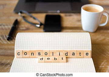 Closeup on notebook over wood table background, focus on wooden blocks with letters making Consolidate Debt words