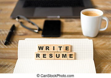 Closeup on notebook over wood table background, focus on wooden blocks with letters making WRITE RESUME words