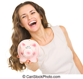 Closeup on piggy bank in hand of smiling young woman