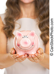 Closeup on piggy bank in hand of young woman
