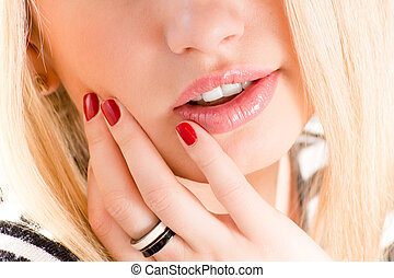 closeup on plump lips of beautiful blonde young woman on a white background with her hand on the pike