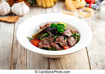 Closeup on roasted beef meat with vegetables