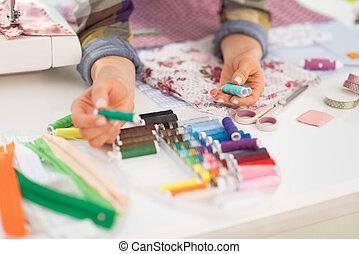 Closeup on seamstress choosing threads
