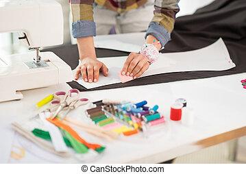 Closeup on seamstress making pattern on fabric