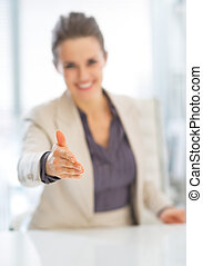 Closeup on smiling business woman stretching hand for...