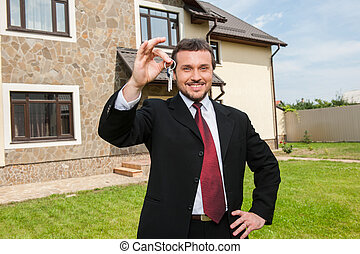 closeup on smiling real estate agent ready to sell house. Male real etate agent in front of home holding keys
