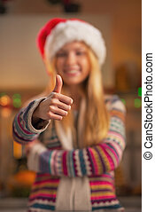 Closeup on smiling teenage girl in santa hat showing thumbs up in christmas decorated kitchen