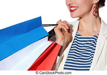 Closeup on smiling woman with French flag colours shopping bags
