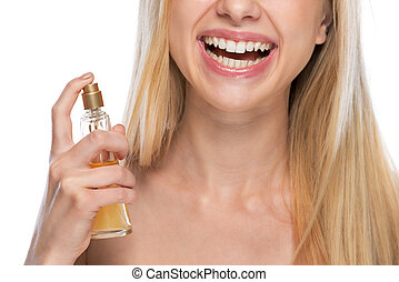 Closeup on smiling young woman applying perfume