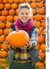Closeup on smiling young woman holding pumpkin