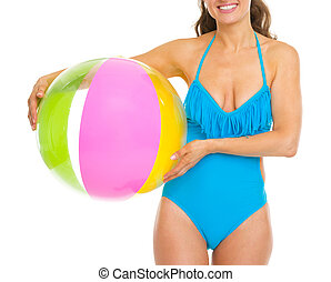 Closeup on smiling young woman in swimsuit with beach ball