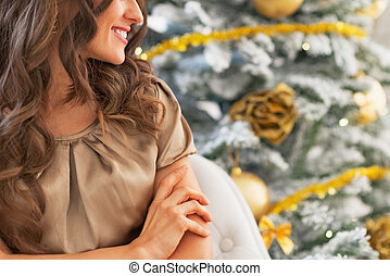Closeup on smiling young woman near christmas tree