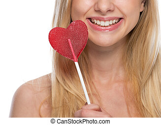 Closeup on smiling young woman with heart shaped lollipop