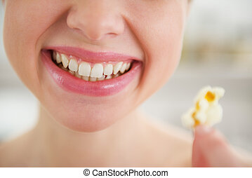 Closeup on smiling young woman with popcorn