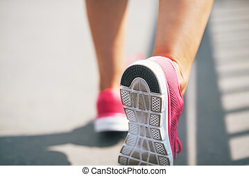 Closeup on sneaker of fitness young woman