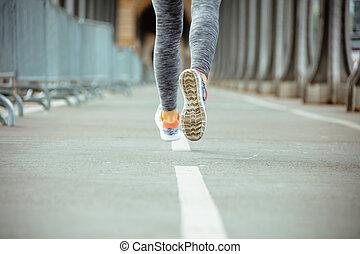 Closeup on sports woman on Pont de Bir-Hakeim bridge jogging