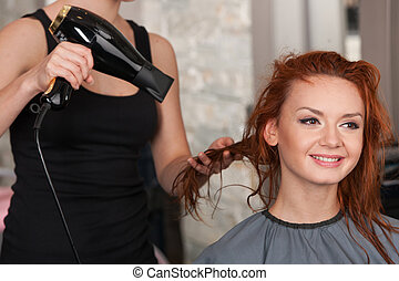 closeup on stylist hands drying redhead woman hair in salon...