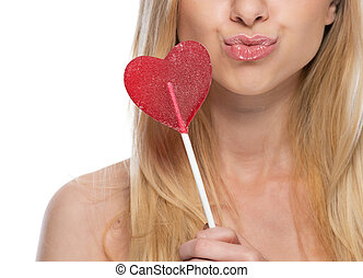 Closeup on thoughtful young woman with heart shaped lollipop
