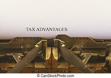 Closeup on vintage typewriter. Front focus on letters making TAX ADVANTAGES text. Business concept image with retro office tool