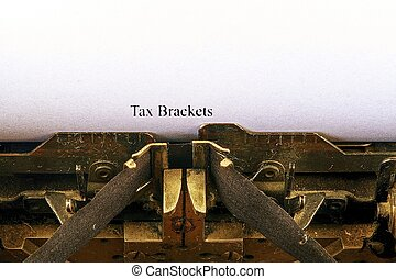 Closeup on vintage typewriter. Front focus on letters making TAX BRACKETS text. Business concept image with retro office tool