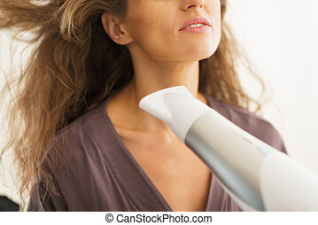 Closeup on woman blow drying hair