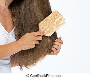 Closeup on woman combing hair