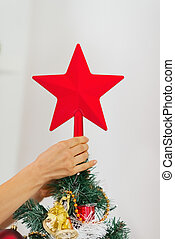 Closeup on woman hand decorating Christmas tree with topper