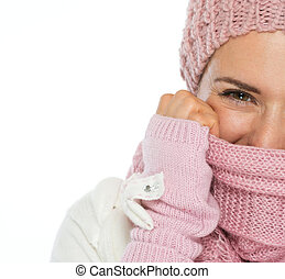 Closeup on woman in knit winter clothing closing face with scarf
