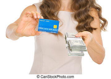Closeup on woman showing credit card and money packs