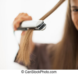 Closeup on woman straightening hair with straightener