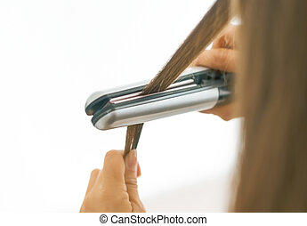 Closeup on woman straightening hair with straightener . rear view