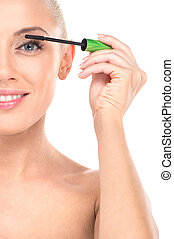 Closeup on young girl mascaras her eyelashes in bathroom. Beauty makeup woman putting mascara eye make up on eyes.