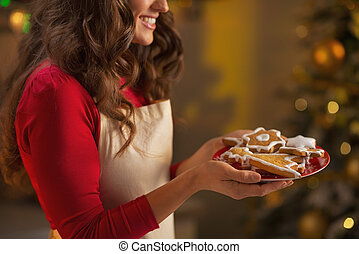 Closeup on young housewife enjoying with plate of christmas cookies