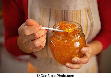 Closeup on young housewife holding homemade orange jam