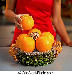 Closeup on young housewife taking orange