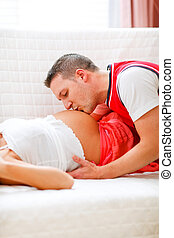 Closeup on young husband kissing his pregnant wifes tummy