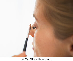Closeup on young woman applying eye shadows