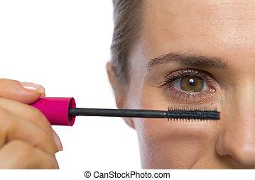 Closeup on young woman applying mascara