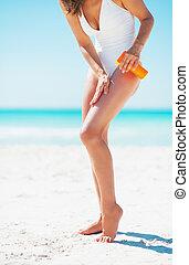 Closeup on young woman applying sun screen creme on beach