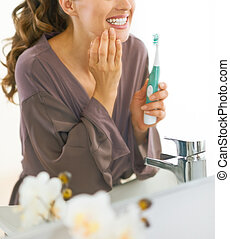 Closeup on young woman checking teeth after brushing
