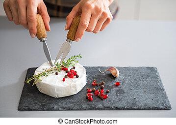 Closeup on young woman eating camembert