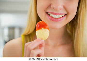 Closeup on young woman eating chips