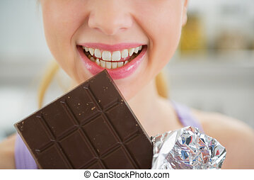Closeup on young woman eating chocolate