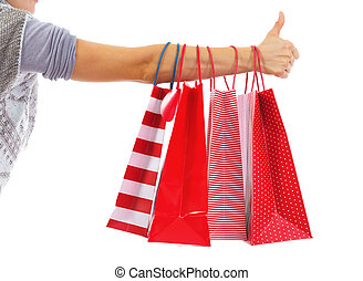 Closeup on young woman hand with christmas shopping bags showing thumbs up