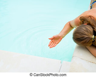 Closeup on young woman playing with water in swimming pool