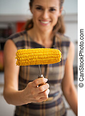 Closeup on young woman showing boiled corn