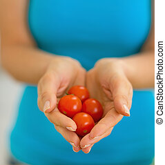 Closeup on young woman showing cherry tomato