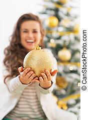 Closeup on young woman showing christmas ball