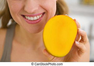 Closeup on young woman showing mango