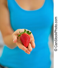 Closeup on young woman showing strawberry